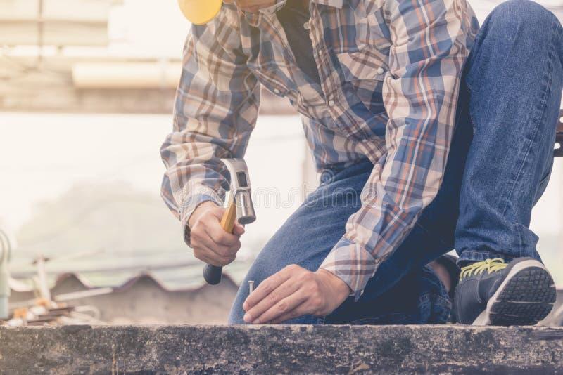 L'homme à l'aide d'un marteau pour clouer le béton photos libres de droits