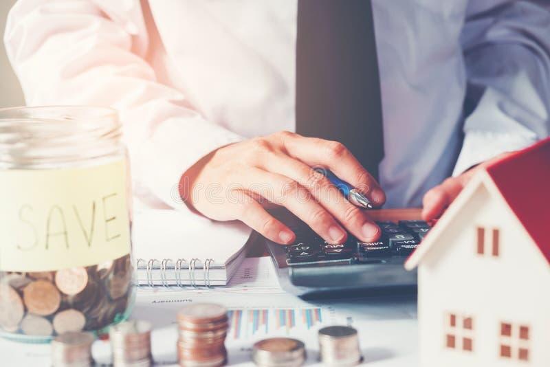 L'homme à l'aide de la calculatrice épargnent l'argent pour le coût à la maison photo stock