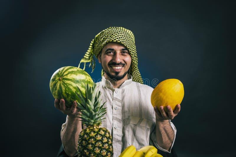l'homme à l'air oriental dans la robe Arabe nationale traditionnelle heureusement sourit et tient le fruit frais images stock