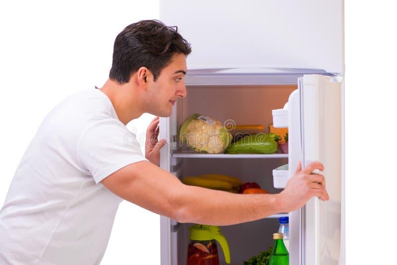 L'homme à côté du réfrigérateur complètement de la nourriture photo libre de droits