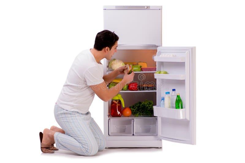 L'homme à côté du réfrigérateur complètement de la nourriture photo stock