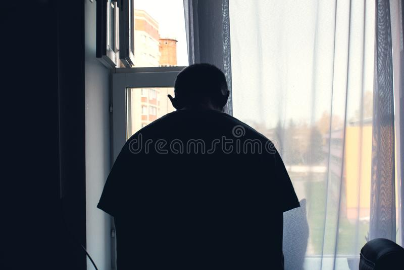 L'homme à la fenêtre, pliant sa tête vers le bas dans la dépression, veut commettre le suicide images stock