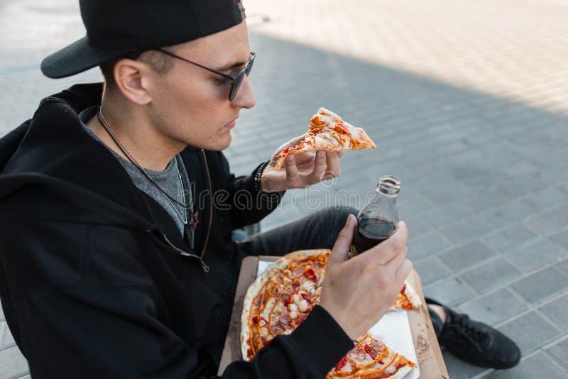L'homme à la mode de jeune hippie beau dans le chapeau élégant dans des lunettes de soleil dans le pull molletonné noir mange de  photographie stock libre de droits