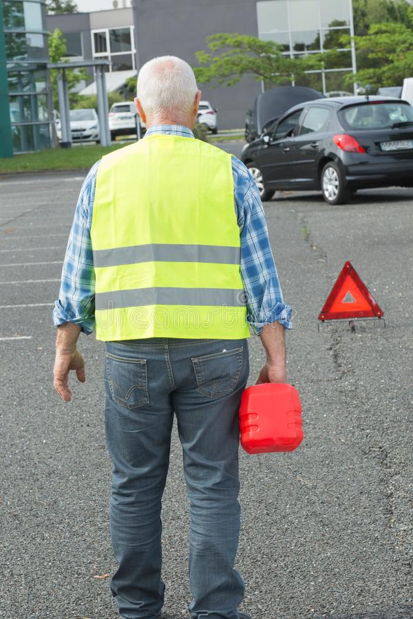 L'homme âgé par aîné tenant le gaz peut remplir la voiture photos stock