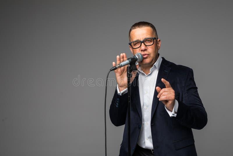 L'homme âgé par milieu heureux et motivé, chantant une chanson avec un microphone, présentant un événement ou ayant une partie, a images libres de droits