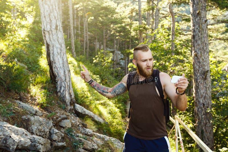 L'homme élégant barbu de randonneur employant la navigation de généralistes pour placer à la traînée de montagne et pense où alle image stock