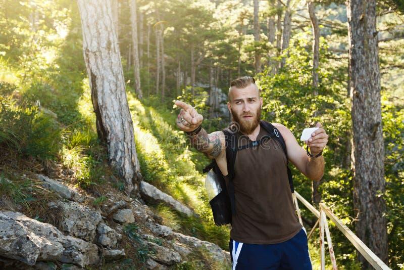 L'homme élégant barbu de randonneur employant la navigation de généralistes pour placer à la traînée de montagne et pense où alle image libre de droits