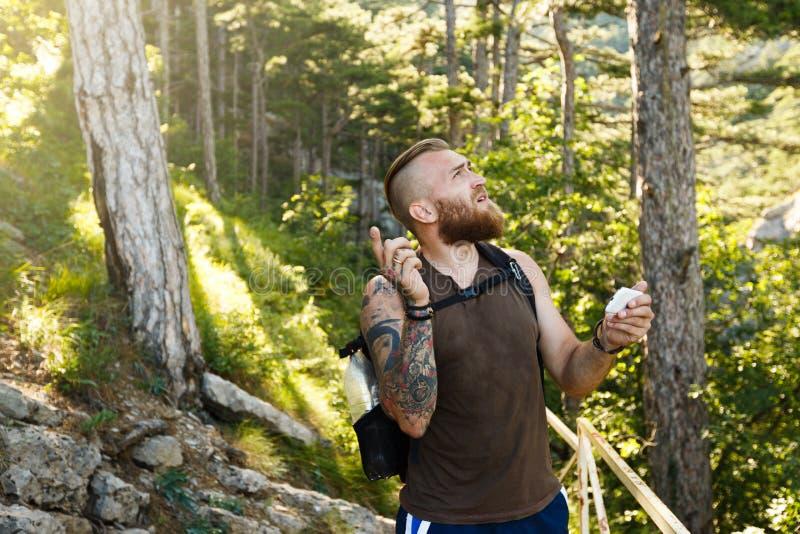 L'homme élégant barbu de randonneur employant la navigation de généralistes pour placer à la traînée de montagne et pense où alle photos stock