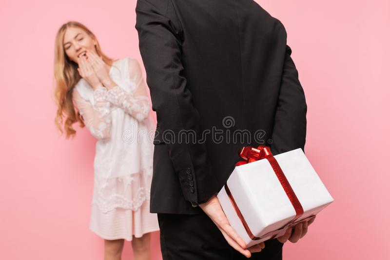 L'homme élégant dans un costume fait une surprise pour une femme, donne un bouquet des fleurs et d'une boîte avec un cadeau, sur  photographie stock
