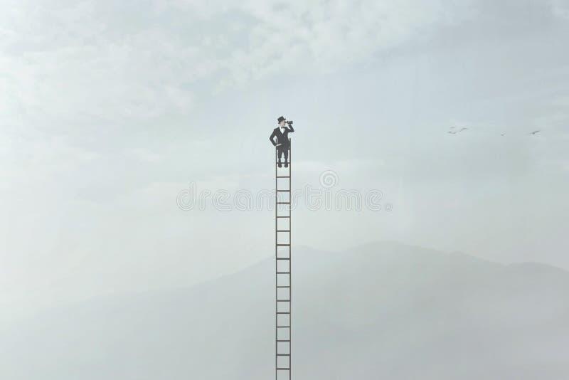 L'homme élégant observe la nature avec son regard en haut d'une échelle très haute image libre de droits