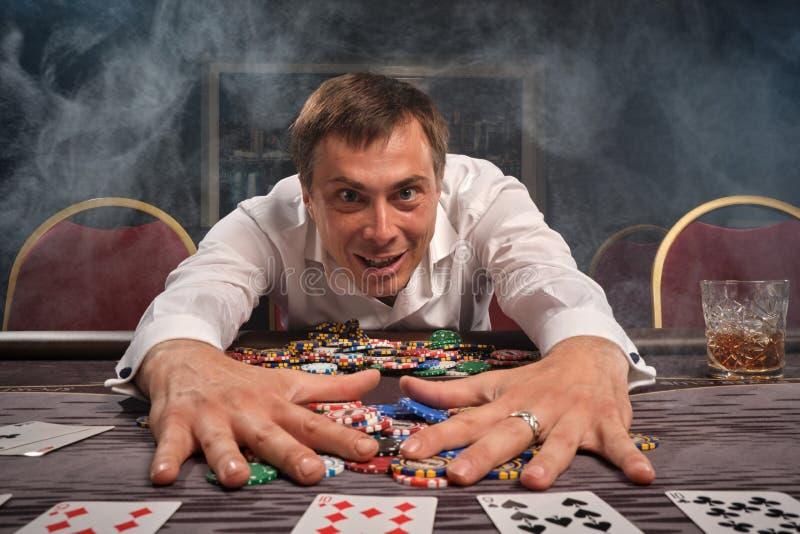 L'homme émotif bel joue au poker se reposant à la table dans le casino photographie stock