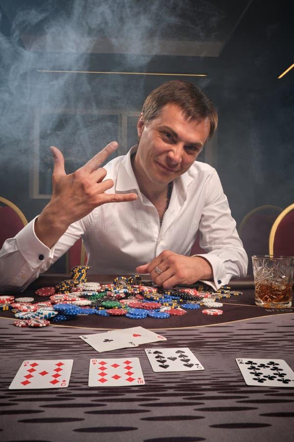 L'homme émotif bel joue au poker se reposant à la table dans le casino photo stock