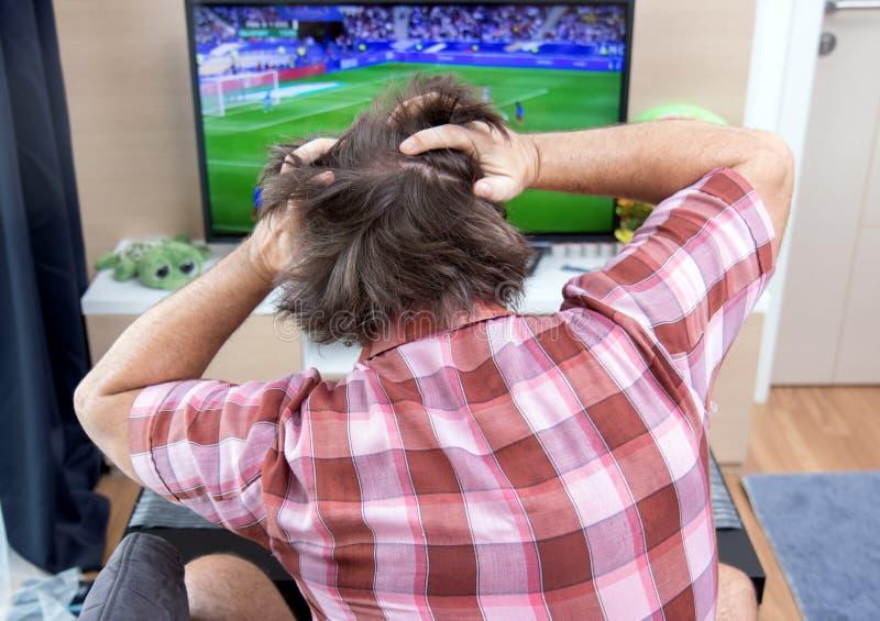 L'homme émotif observe le football dans la TV photographie stock libre de droits