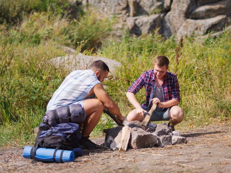 L'homme établit le feu Pit Around Open Camp Fire photos stock