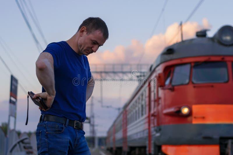 L'homme était en retard pour les supports de train avec sa tête vers le bas photo libre de droits