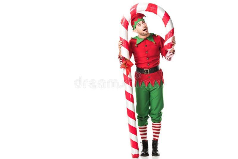 l'homme étonné dans la position de costume d'elfe de Noël sous la grande canne de sucrerie a isolé photo stock