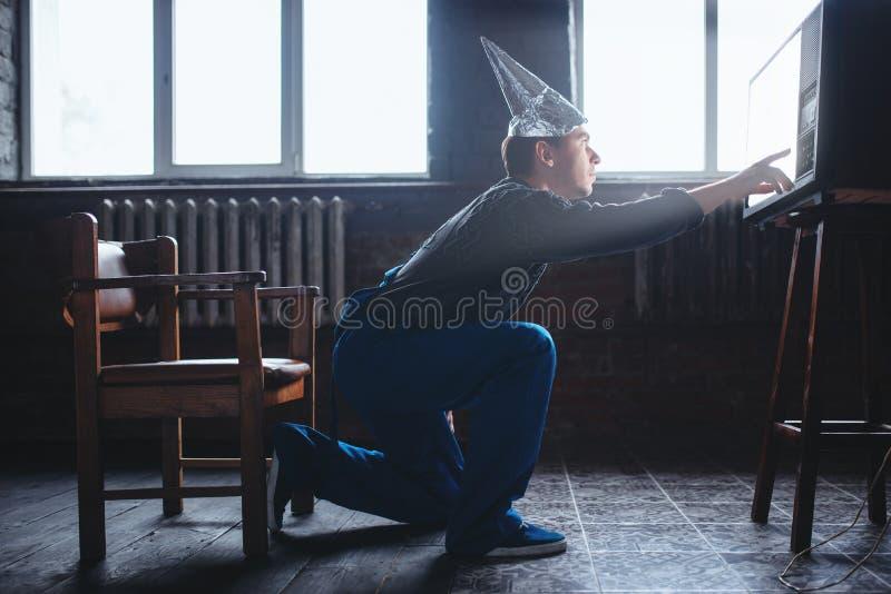 L'homme étrange dans le chapeau de feuille d'étain atteint à TV, UFO images stock