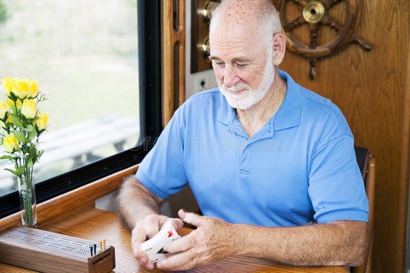 L'homme aîné bat des cartes images libres de droits