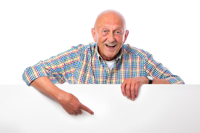 L'homme aîné de sourire heureux retient un panneau blanc photos libres de droits