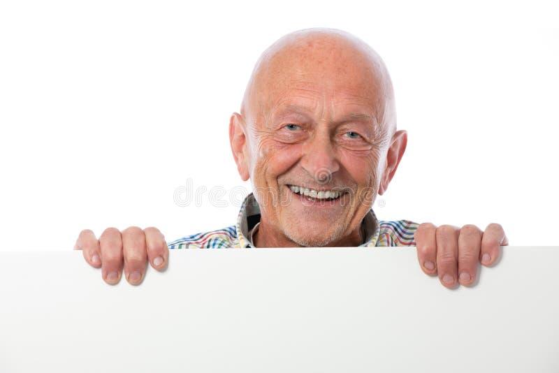 L'homme aîné de sourire heureux retient un panneau blanc image libre de droits