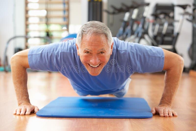 L'homme aîné faisant la presse se lève photo stock