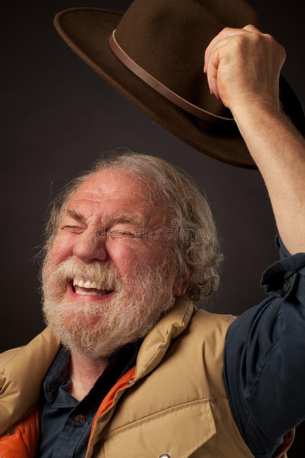 L'homme aîné ondule joyeux le chapeau en air images libres de droits