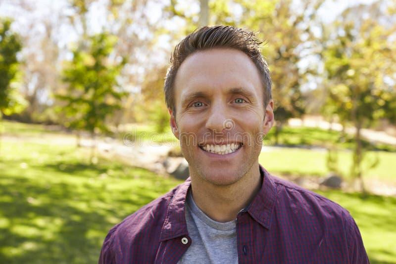 L'homme adulte blanc heureux en parc regardant à l'appareil-photo, se ferment  photos stock