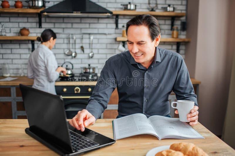L'homme adulte gai s'asseyent à la table dans la cuisine Il regardent sur l'ordinateur portable et le touchent Tasse de prise de  images libres de droits