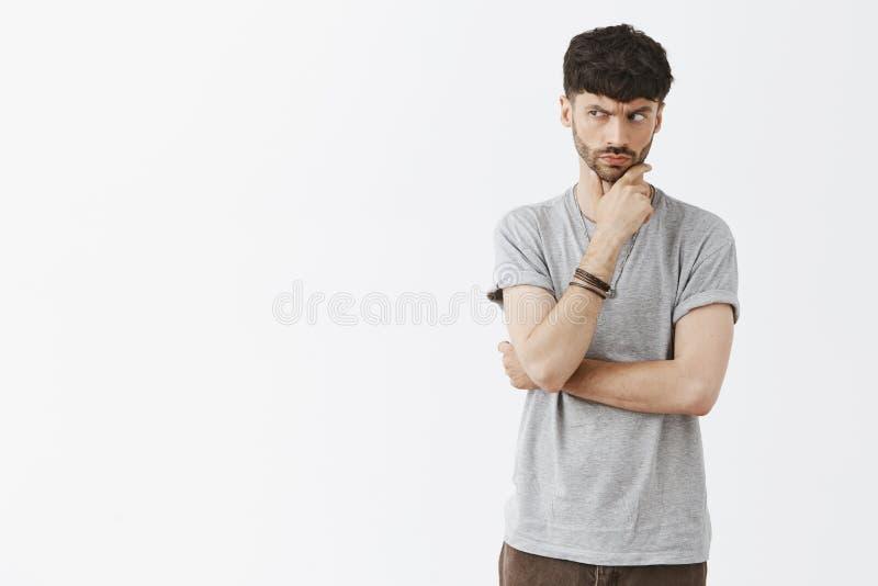 L'homme adulte méfiant avec la barbe fronçant les sourcils et regardant fixement avec l'incrédulité et le doute est parti, étant  photos libres de droits