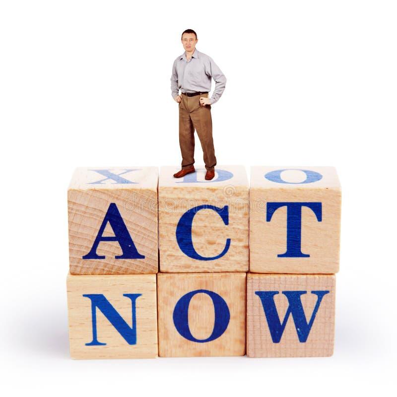 L'homme adulte se tient sur un tas des blocs en bois avec un acte d'appel maintenant images libres de droits