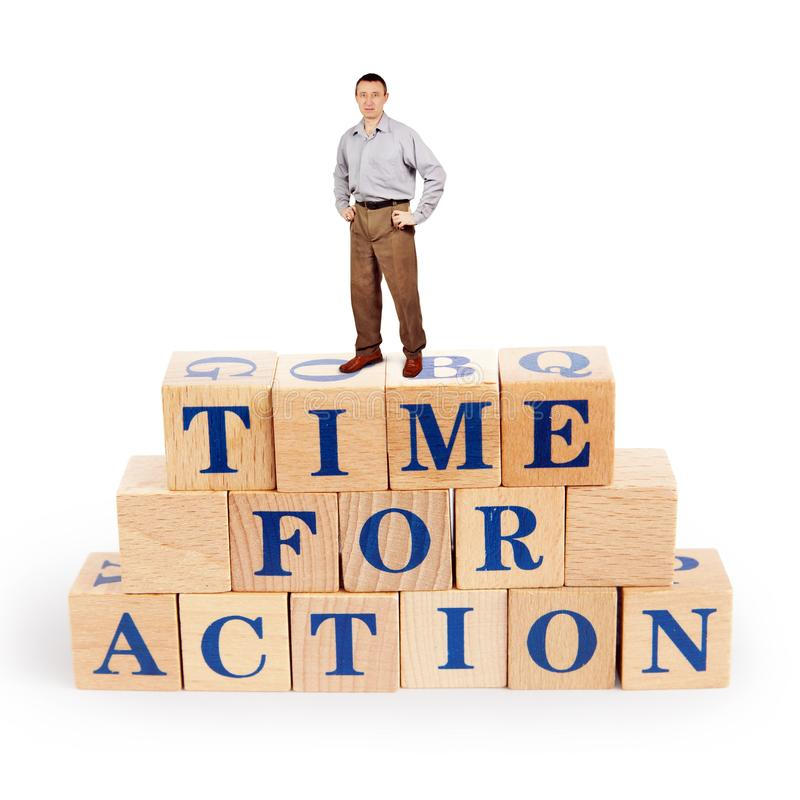 L'homme adulte se tient sur un tas des blocs en bois avec du temps d'appel pour l'action images stock