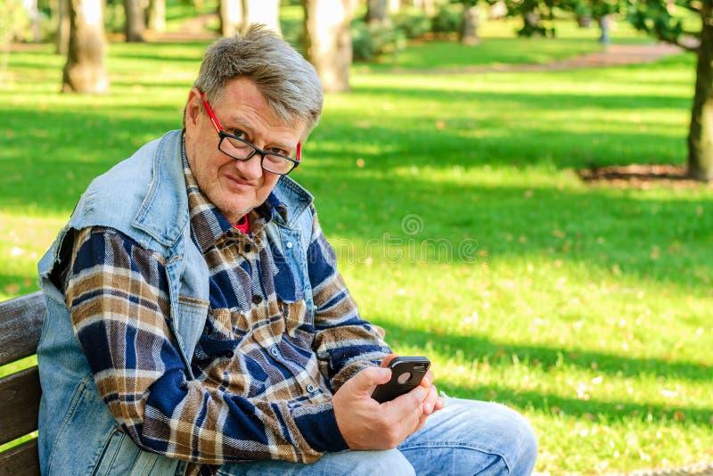 L'homme adulte supérieur dans les vêtements décontractés et des lunettes, s'assied sur a images stock