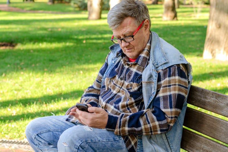 L'homme adulte supérieur dans les vêtements décontractés et des lunettes, s'assied sur a image libre de droits