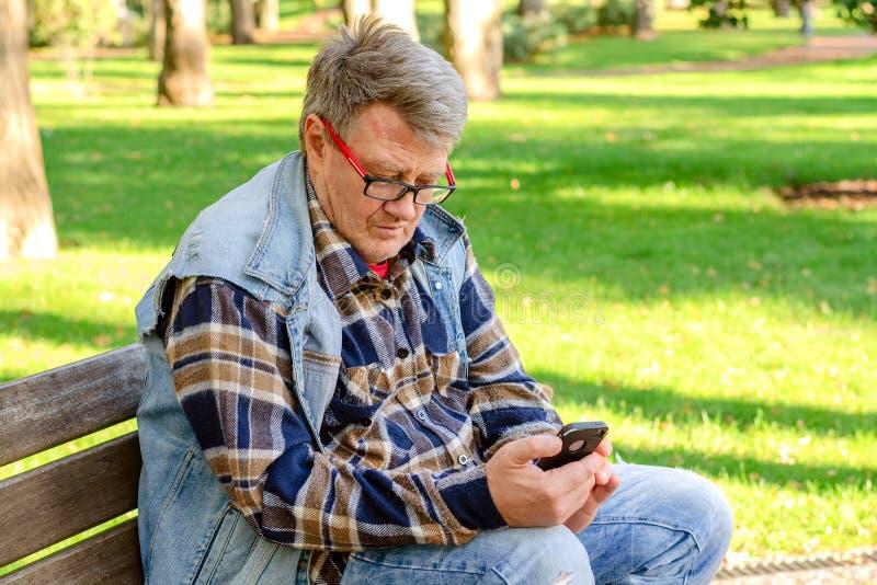 L'homme adulte supérieur dans les vêtements décontractés et des lunettes, s'assied sur a photographie stock