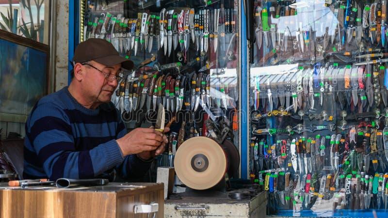 L'homme affile le couteau au bazar images stock