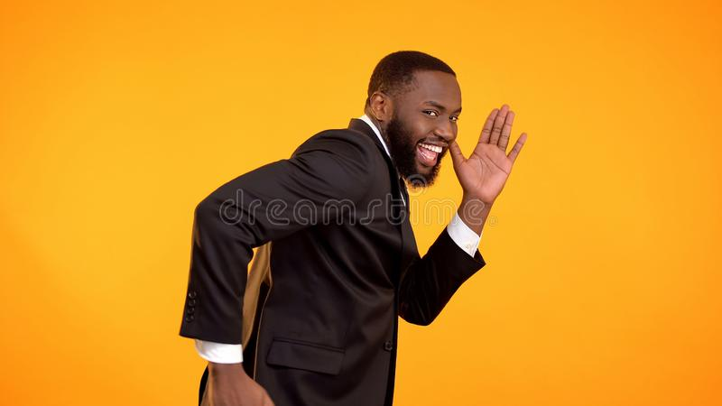L'homme afro-am?ricain bel joyeux feignent courant, vente noire de vendredi, remises photographie stock libre de droits