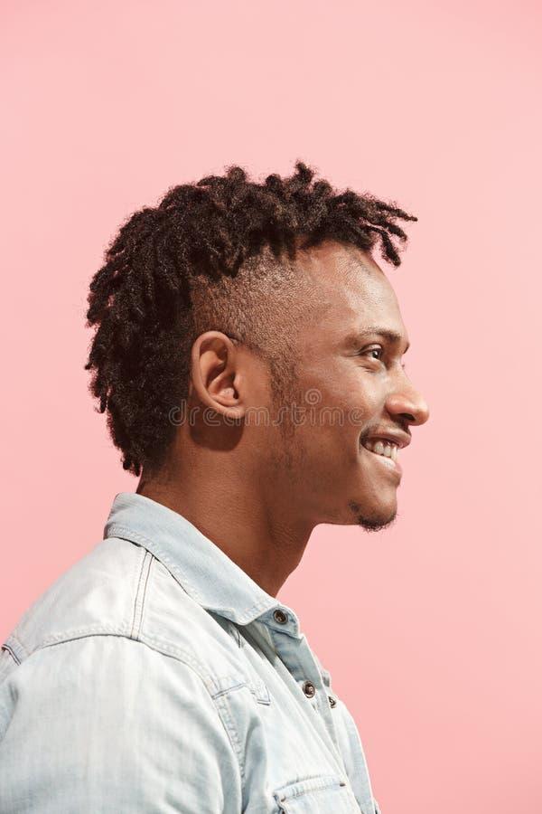 L'homme afro-américain d'affaires heureuses se tenant et souriant sur le fond rose Vue de profil photographie stock libre de droits