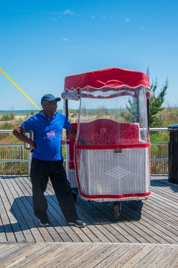 L'homme afro-américain noir qui pousse une chaise de roulement célèbre attend un touriste pour demander un tour sur la promenade  photographie stock libre de droits