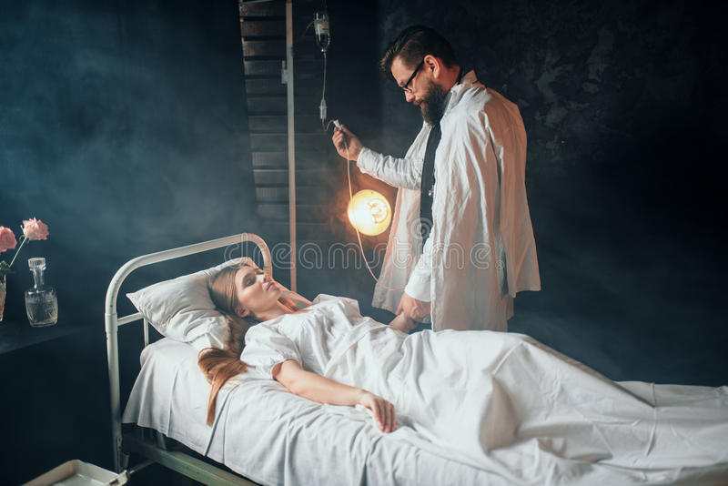 L'homme ajuste l'égouttement de la femme malade dans l'hôpital photographie stock libre de droits