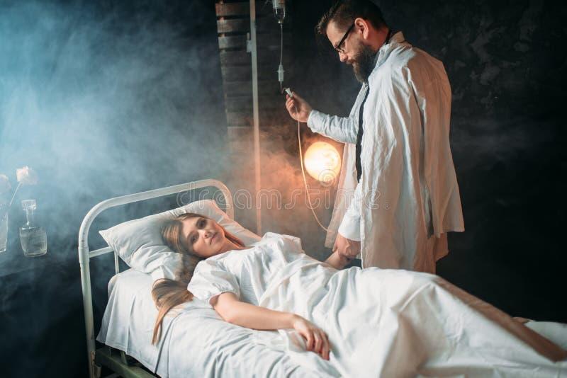 L'homme ajuste l'égouttement de la femme malade dans l'hôpital images libres de droits