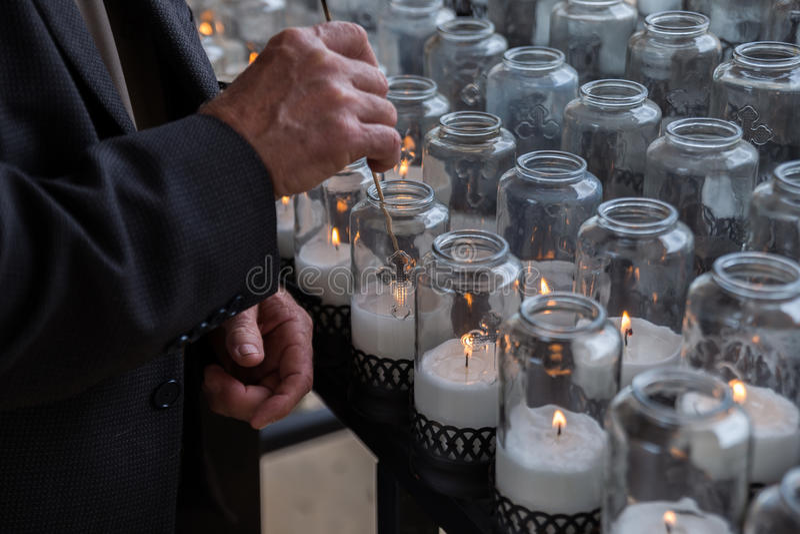 L'homme allume des bougies dans une église catholique photo libre de droits