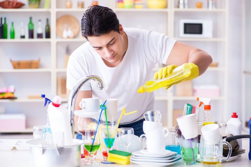 L'homme appréciant des corvées de lavage de plat à la maison photographie stock