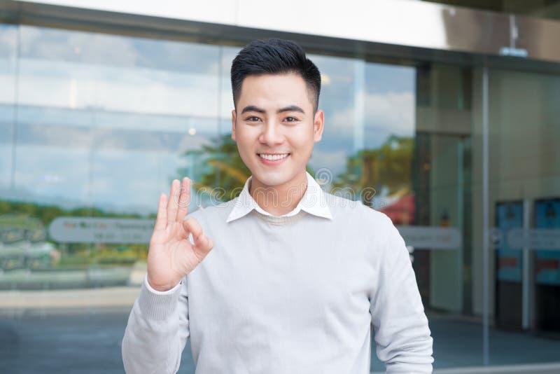 L'homme asiatique bel montrant la main correcte signent dehors photos libres de droits