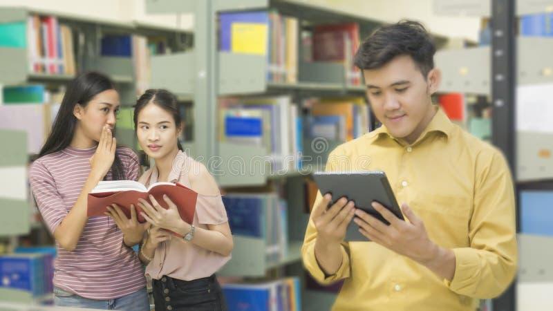 L'homme asiatique d'adolescent lit un comprimé avec des filles parlent au livre SH image libre de droits