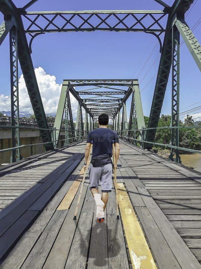L'homme asiatique a employé des promenades de béquilles sur la structure métallique de pont en bois à travers Pai River, Phitsanu photographie stock libre de droits