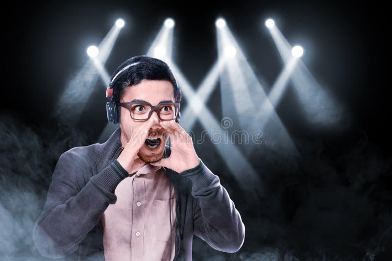 L'homme asiatique expressif en verres utilisant la veste brune apprécient la musique avec des écouteurs images libres de droits
