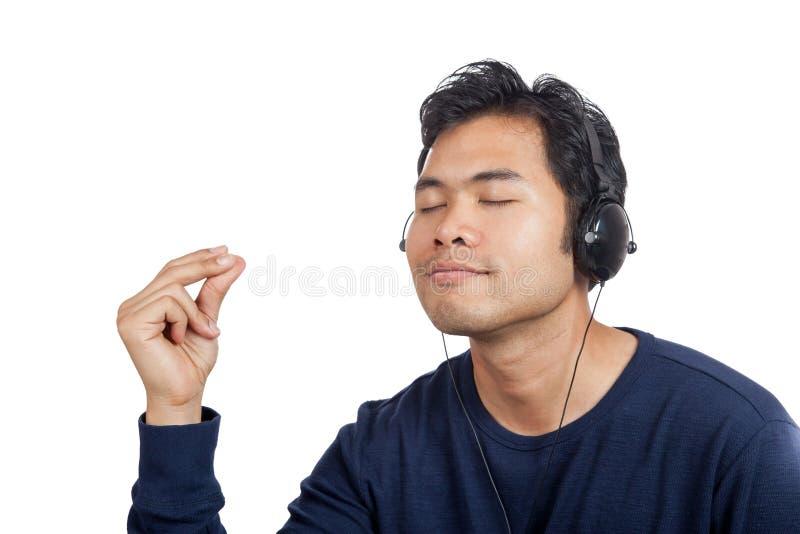 L'homme asiatique heureux écoutent la musique font la rupture de doigt photos stock