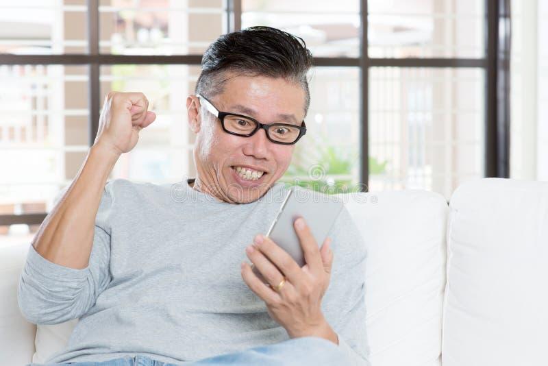 L'homme asiatique mûr célèbre le succès tout en à l'aide du smartphone photographie stock libre de droits