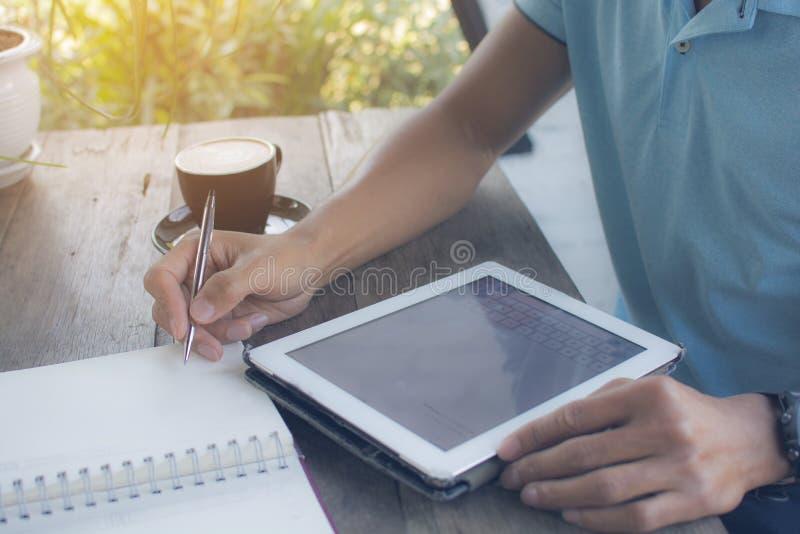 L'homme asiatique a mis un stylo au carnet pour travailler avec le bloc-notes sur photo stock