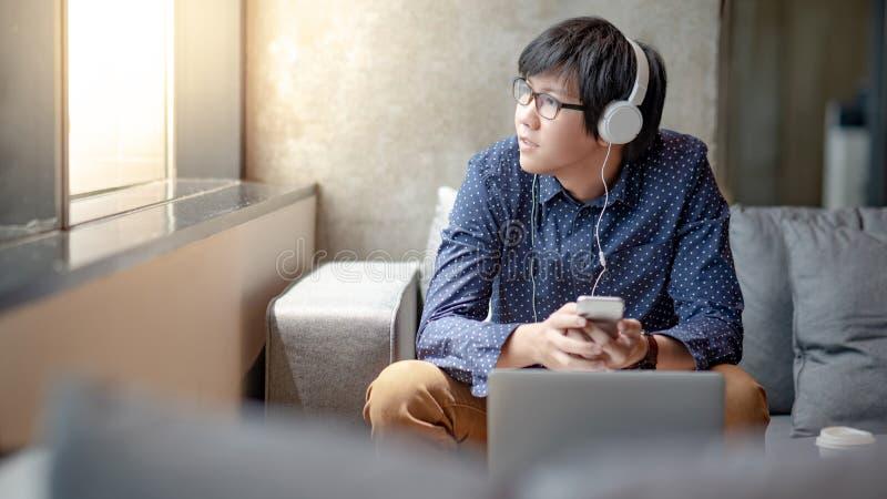 L'homme asiatique ont plaisir à écouter la musique sur le sofa photographie stock libre de droits